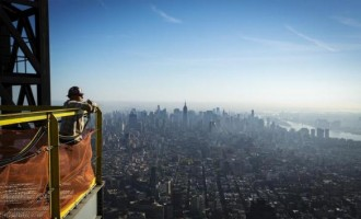 Iron worker Tyler Brown leans on a safety fence to look at the New York skyline