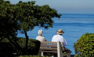 An elderly couple looks out at the ocean as they sit on a park bench in La Jolla