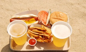 A hot dog, hamburger, french fries and two glasses of Peroni