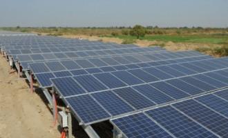 An employee walks past solar panels plac