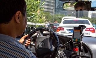 A taxi driver is using Didi Dacha App