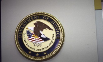 Justice department seal hanging on wall.